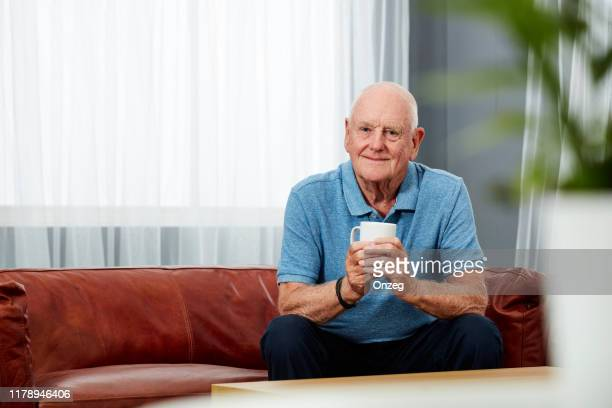 senior man with a cup of coffee at home - one man only stock pictures, royalty-free photos & images