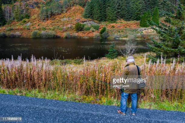 senior man with a fly fishing rod next to a scottish loch - johnfscott stock pictures, royalty-free photos & images