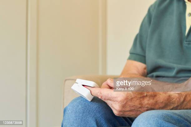 senior man with a pulse oximeter device on his finger - medical oxygen equipment stock pictures, royalty-free photos & images