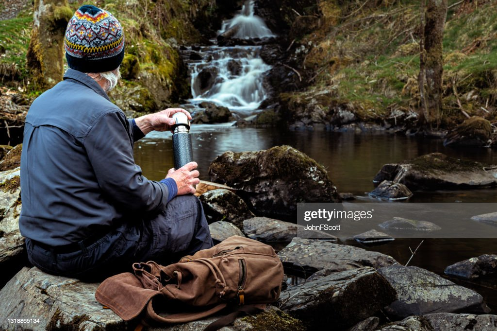 Senior man with a thermos flask at a waterfall : Stock Photo
