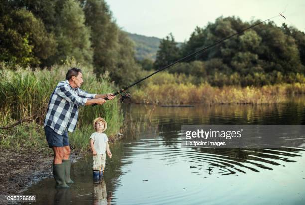 a senior man with a toddler boy fishing together on a lake. copy space. - 淡水釣り ストックフォトと画像