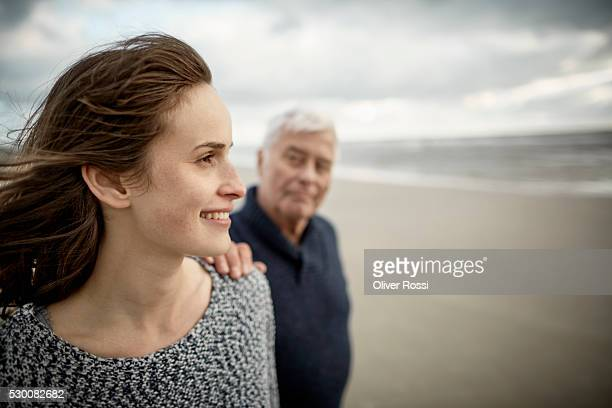 senior man with adult daughter on the beach - old man young woman stock photos and pictures