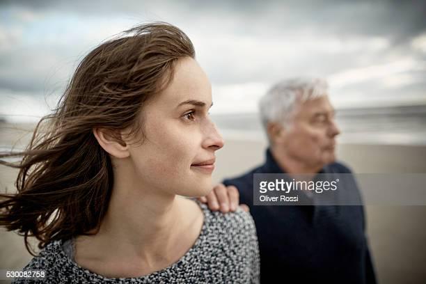 senior man with adult daughter on the beach - pareja hombre mayor y mujer joven fotografías e imágenes de stock