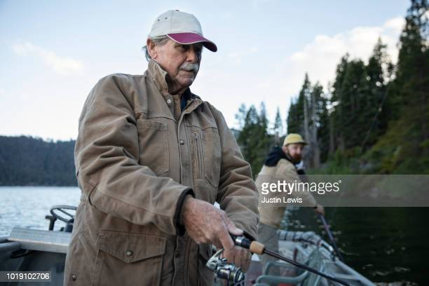 Senior Man with Adult Grandson Fishing on a Mountain Lake with Their Boat