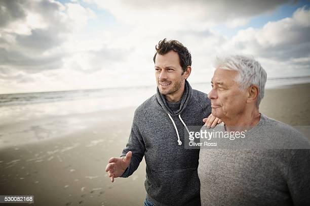 Senior man with adult son on the beach