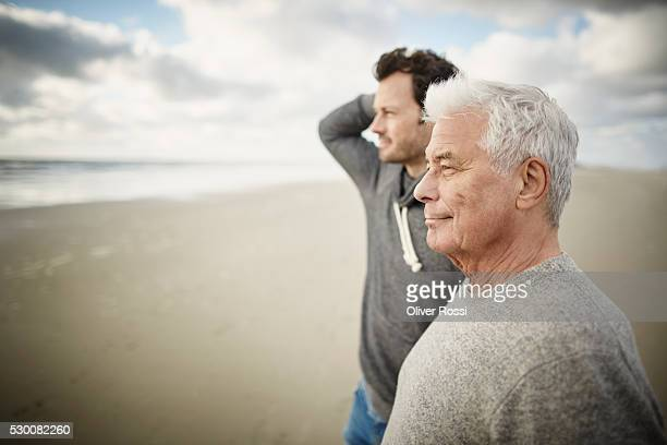 Senior man with adult son on the beach