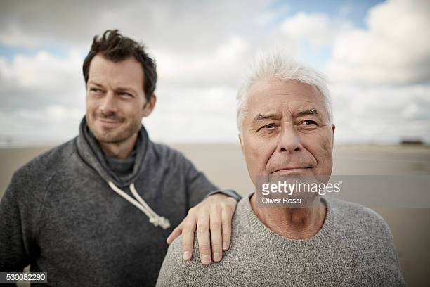 senior man with adult son on the beach - hand on shoulder stock pictures, royalty-free photos & images