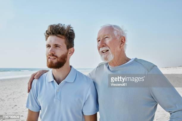 senior man with adult son on the beach - senior adult stock-fotos und bilder