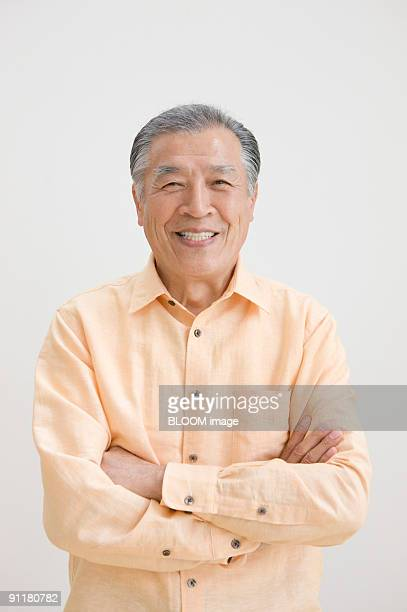 senior man with arms folded, portrait - 60代 ストックフォトと画像