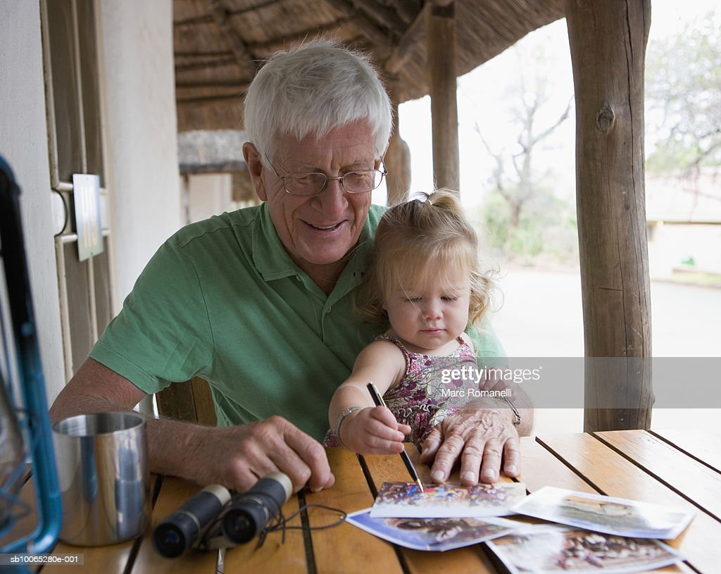 Senior man with baby girl (9-12 months) sitting together at table : Foto stock