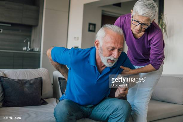 senior man with backache - backache stock pictures, royalty-free photos & images