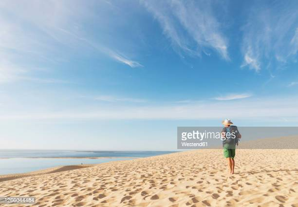 senior man with backpack looking at atlantic ocean while standing on beach, dune of pilat, nouvelle-aquitaine, france - gironde stock pictures, royalty-free photos & images