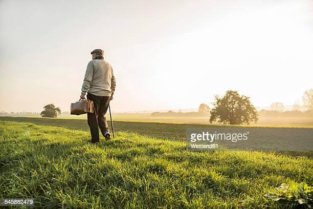 Senior man with bag walking in rural landscape