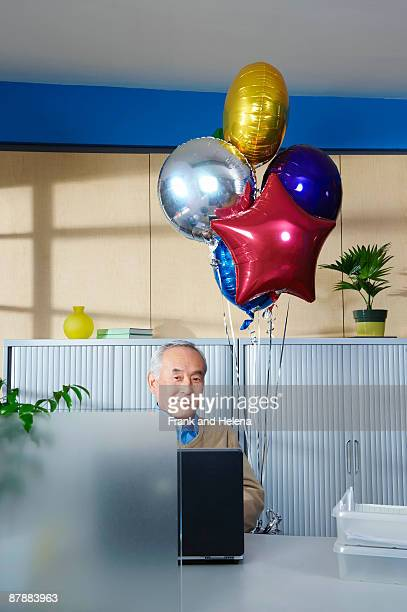 Senior man with balloons at office desk