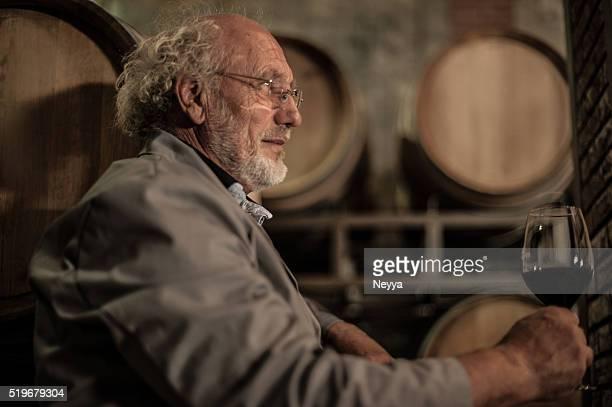 Senior homme avec barbe tenant un verre de vin rouge