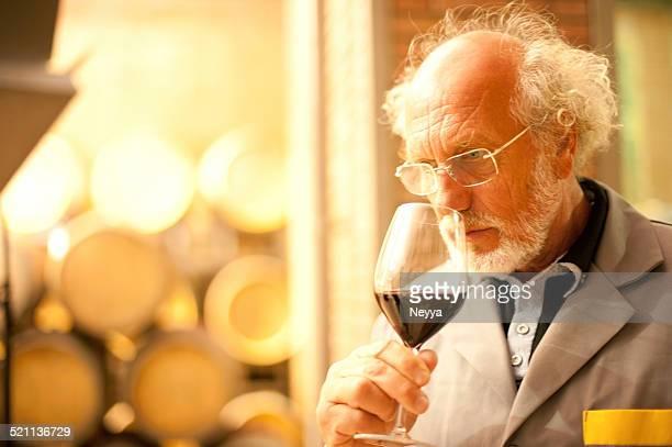 Hombre mayor con barba sostiene una copa de vino tinto