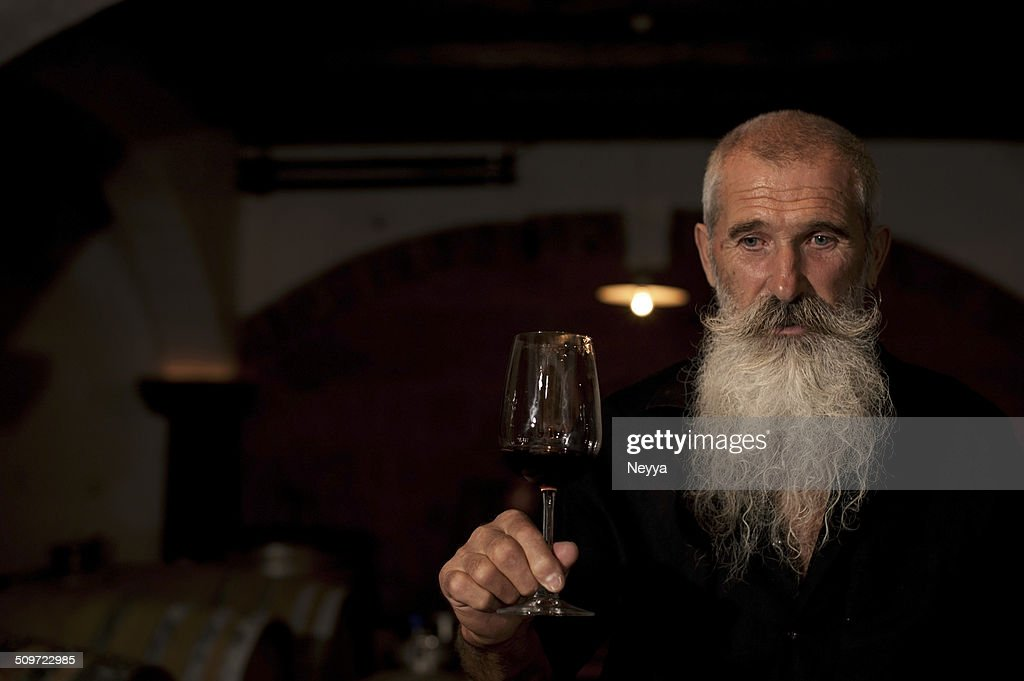 Senior Man with Beard Holding Glass of  Wine in Winecellar : Stock Photo