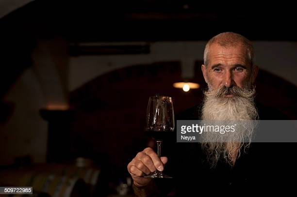 Senior Man with Beard Holding Glass of  Wine in Winecellar