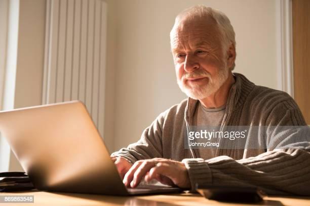ひげのラップトップを見て、キーボードで入力すると年配の男性