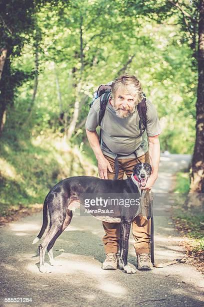 senior man with beard - mountaineer and his greyhound dog - named animal ストックフォトと画像