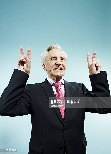 A senior man with both hands raised making peace signs