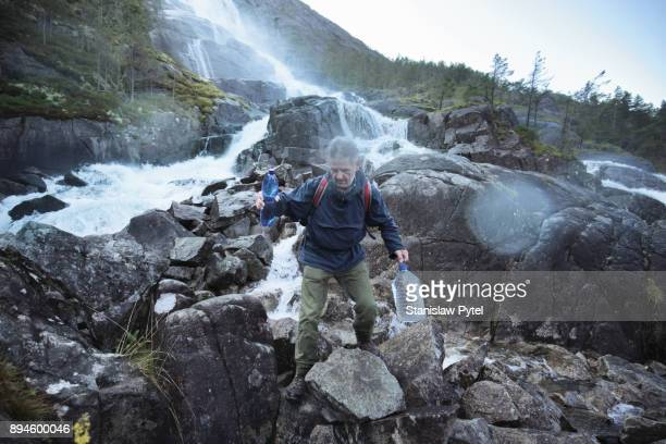 Senior man with bottles filled with fresh water from waterfall