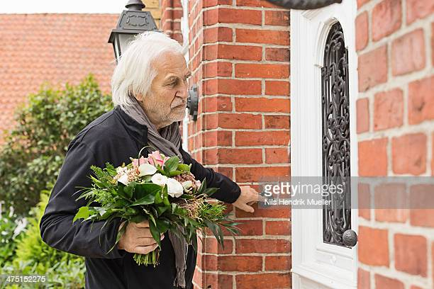 Senior man with bouquet ringing doorbell