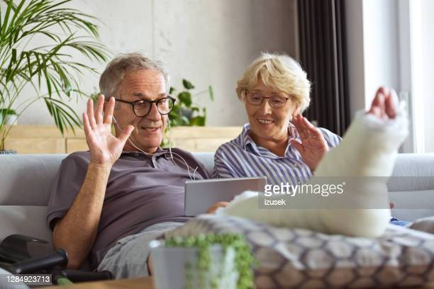 senior man with broken leg at home and  his wife - old man feet stock pictures, royalty-free photos & images