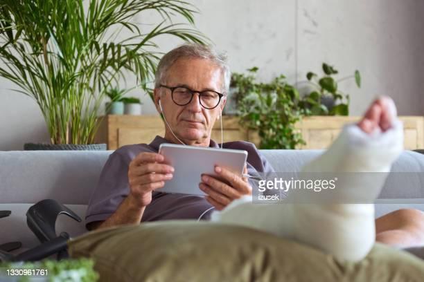senior man with broken leg at home - izusek stockfoto's en -beelden