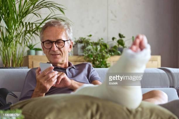 senior man with broken leg at home - human leg stock pictures, royalty-free photos & images