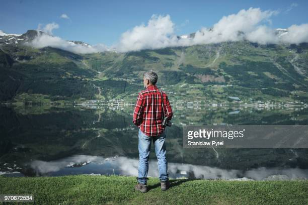 Senior man with camera against beautiful view on mountains and ocean