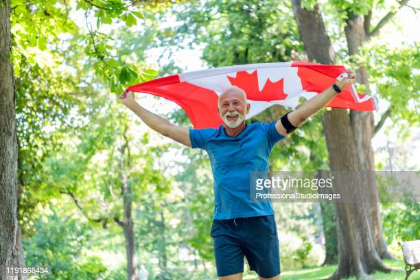 senior man with canadian flag in public park - canada day stock pictures, royalty-free photos & images