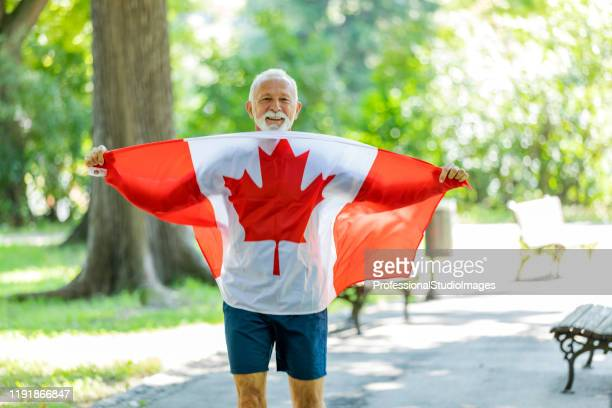 senior man with canadian flag in public park - canadian culture stock pictures, royalty-free photos & images
