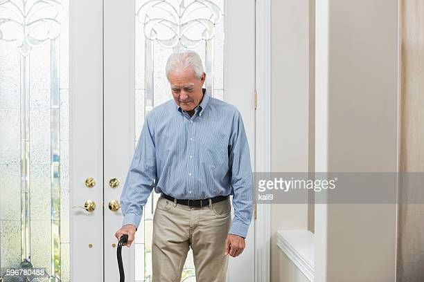 Senior man with cane coming home