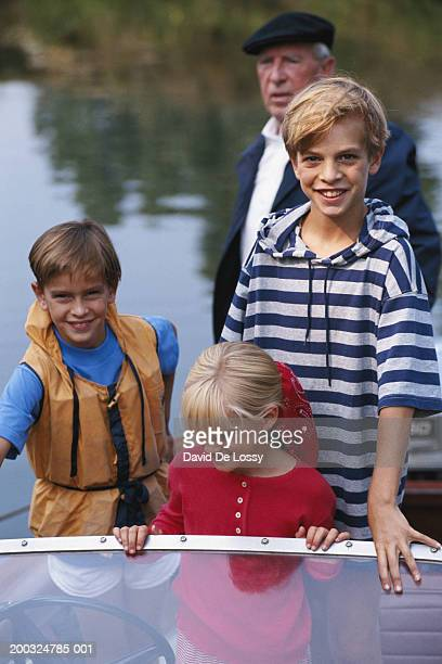 senior man with children (6-11) in motor boat - bang boat stock pictures, royalty-free photos & images