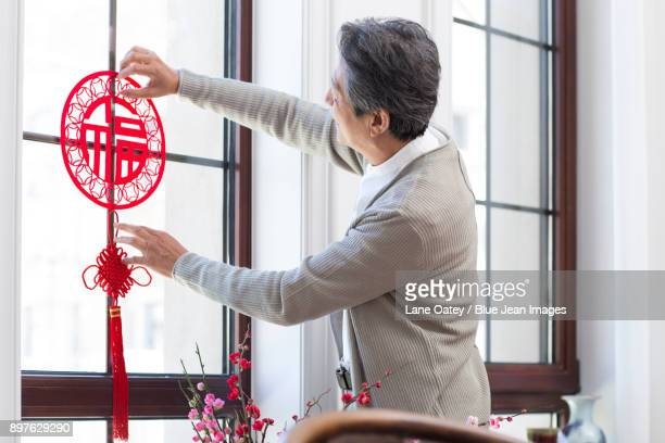 senior man with chinese new year paper-cut - chinese knotting stock pictures, royalty-free photos & images