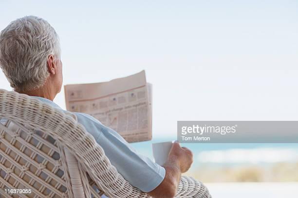 Alter Mann mit Kaffee und Tageszeitung am Strand und Terrasse
