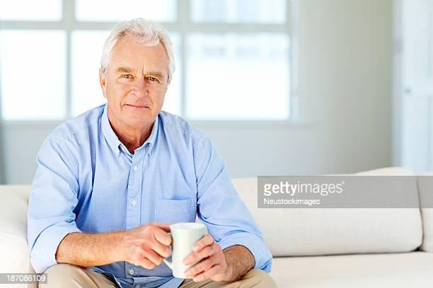 senior hombre con una taza de café, sentado en el sofá en casa - 60 64 años fotografías e imágenes de stock