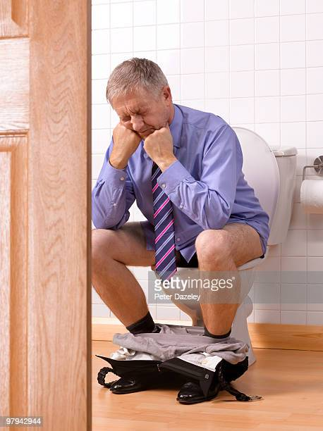 Senior man with constipation IBS in bathroom