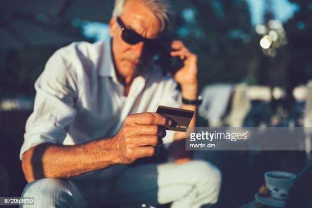 Ältere Mann mit Aufruf der Bankhaus Kreditkarte
