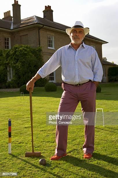 Senior man with croquet set.