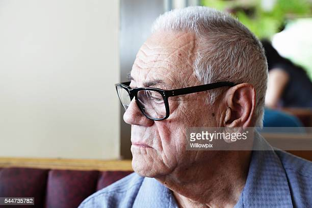 Senior Man With Dementia Sitting Alone in Restaurant Looking Down