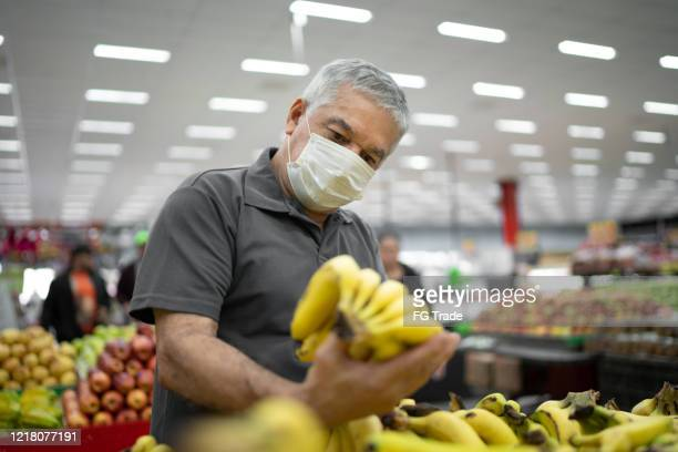 senior man with disposable medical mask shopping in supermarket - groceries stock pictures, royalty-free photos & images