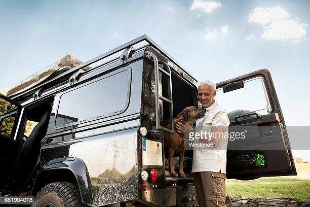 Senior man with dog at cross country vehicle