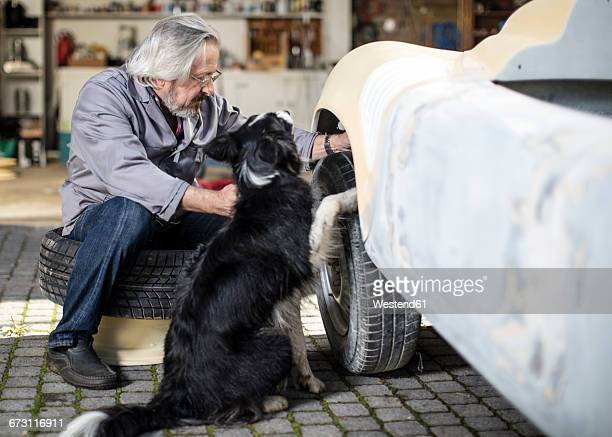 Senior man with dog examining car tyre