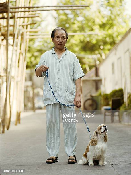 Senior man with dog on leash, portrait