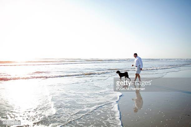 Senior man with dog walking on beach