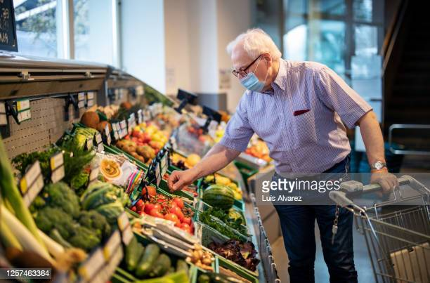 senior man with face mask buying vegetables in grocery store - supermarket stock pictures, royalty-free photos & images