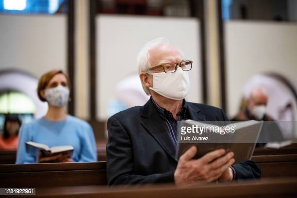 senior man with face mask for religious mass at church - christianity stock pictures, royalty-free photos & images