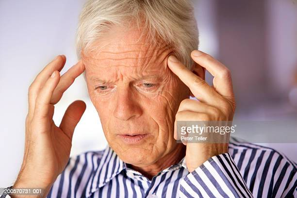 senior man with fingers on temples, close-up - schmerz stock pictures, royalty-free photos & images